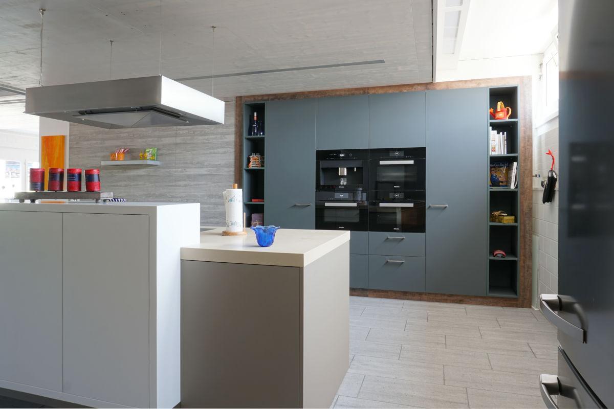 Ein weisses Möbel bildet seitlich den Abschluss der Küche. Es bietet Stauraum für Geschirr oder ähnliches.