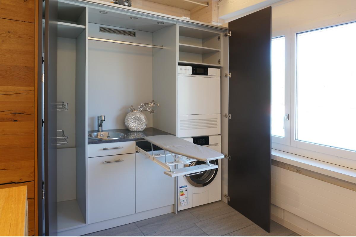 Hinter der Schranktür verbirgt sich die Hauswirtschaftszone mit Waschmaschine, Trockner und ausziehbarem Bügelbrett.