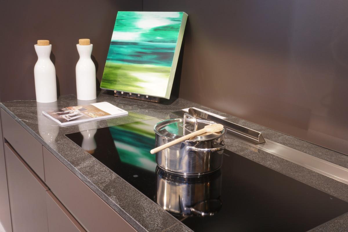 Das Glaskeramik-Kochfeld von Electrolux ist flächenbündig in die Granitplatte eingesetzt .