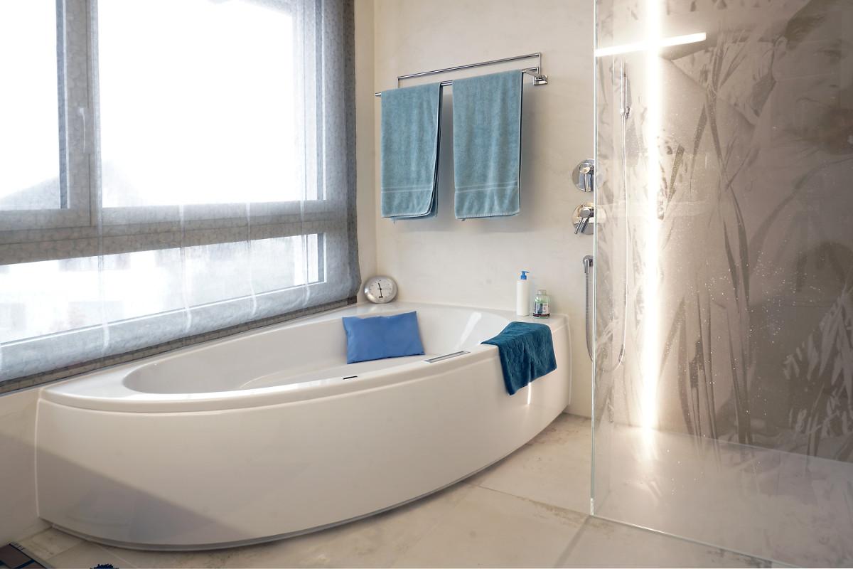 Modernes Badezimmer mit Badewanne und Duschkabine. Die Leuchtschine ist direkt in die Wand eingelassen.