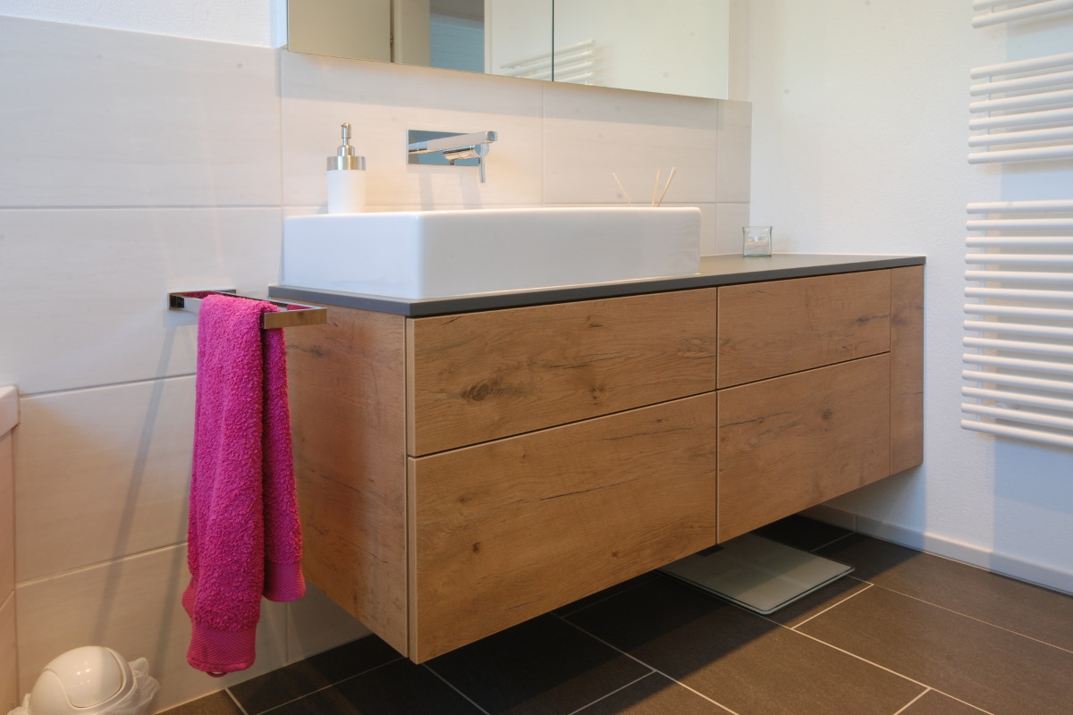 Badezimmermöbel im Altholz-Look mit rosarotem Handtuch