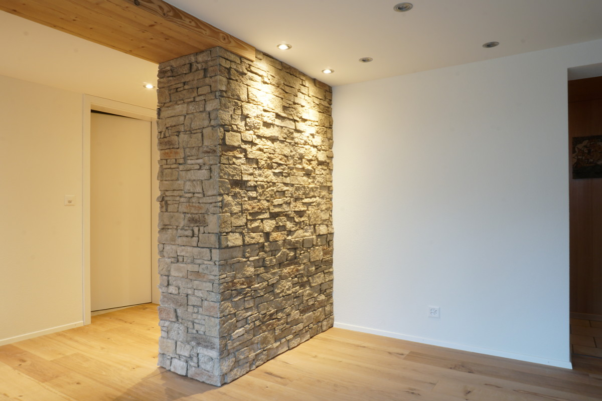 Wandverkleidung: Die künstliche Steinmauer auf dem schönen Holzparkett bewirkt ein rustikales Erscheinungsbild.