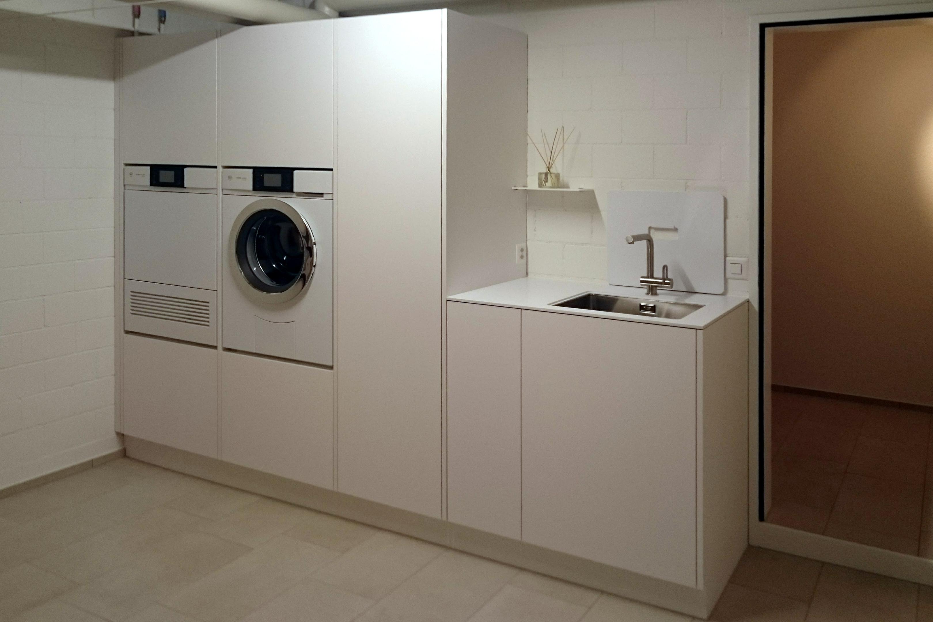 Schöne und praktische Waschkücheneinrichtung in dezentem Weiss.
