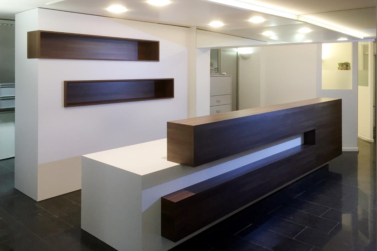 Schalteranlage einer Tierarztpraxis. Die dunklen Holzelemente stehen in schönem Kontrast zu den weissen Wänden und Möbeln.
