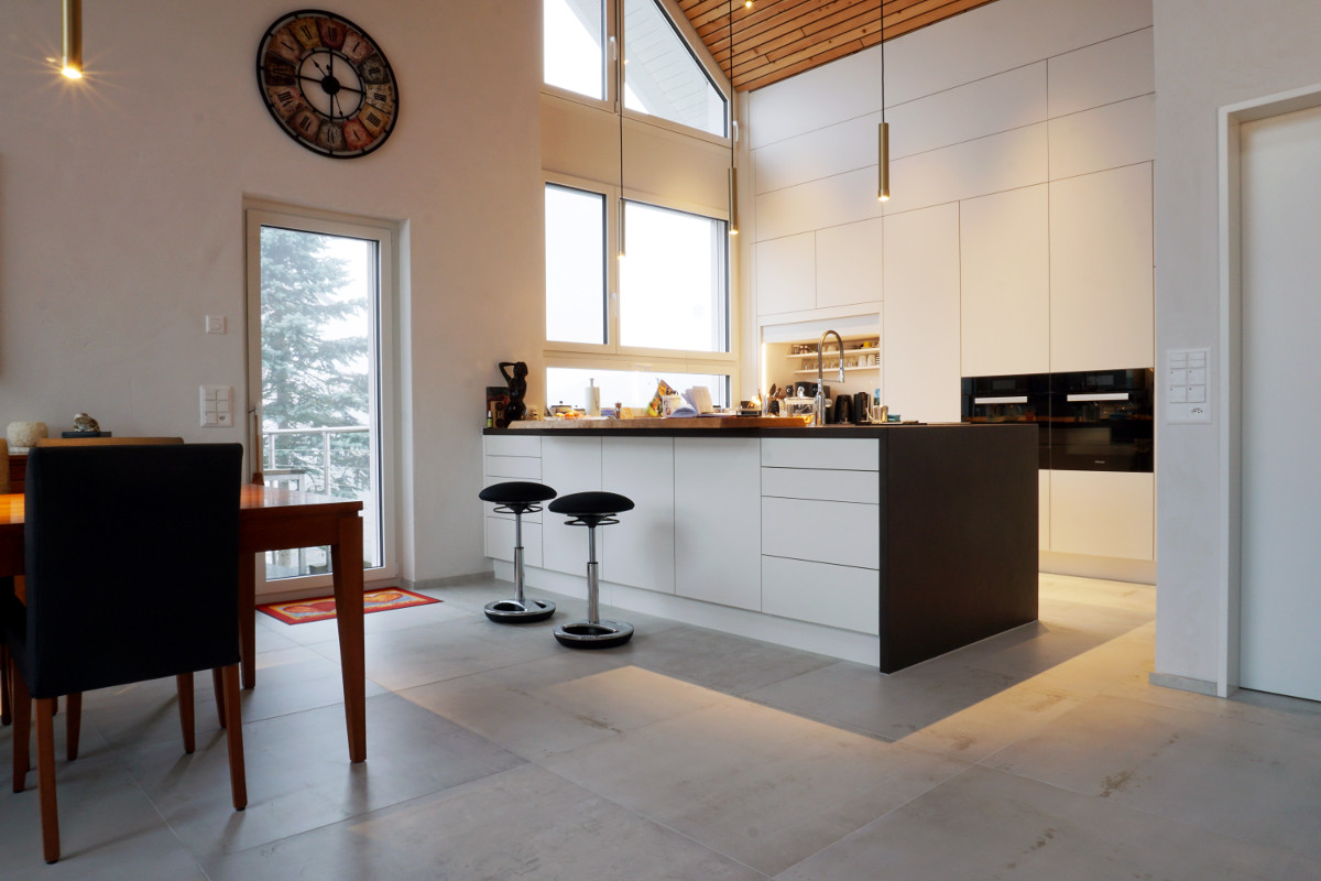 Grosszügige Wohnküche mit Kochinsel und aufgesetztem Altholz-Brett als Bartheke. Die hoch liegenden Wandschränke lassen sich per Fernbedienung öffnen.