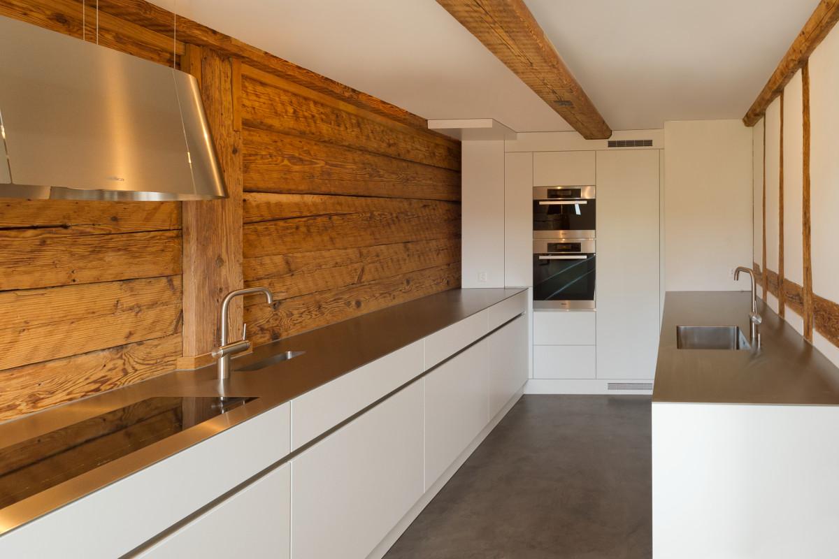 Weisse zweireihige Küche in altem Bauernhaus mit Altholz-Täferung. Chromstahlabdeckung, Glaskeramik-Kochfeld und frei hängender Dunstabzugshaube.
