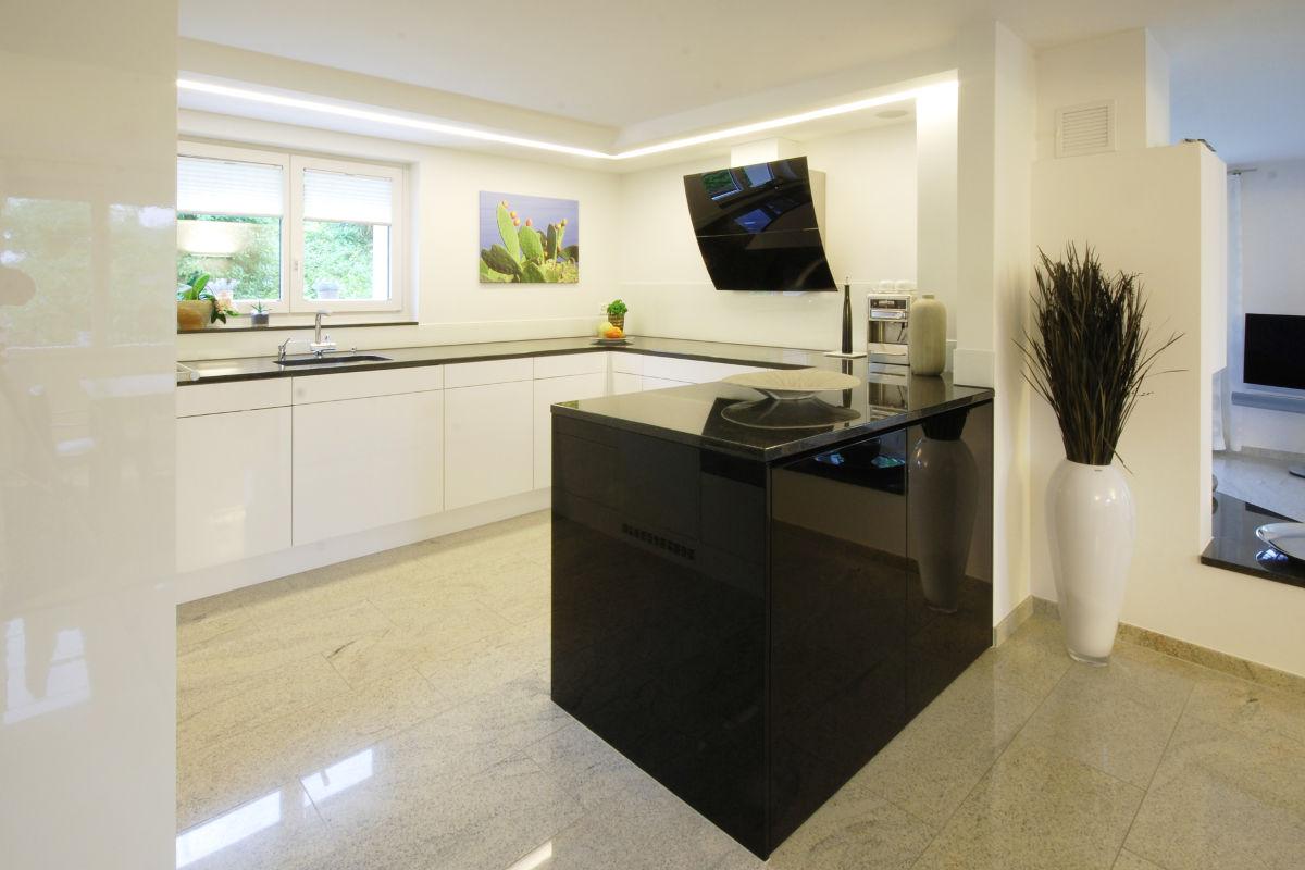 Weisse Hochglanzküche mit schwarzem Granit
