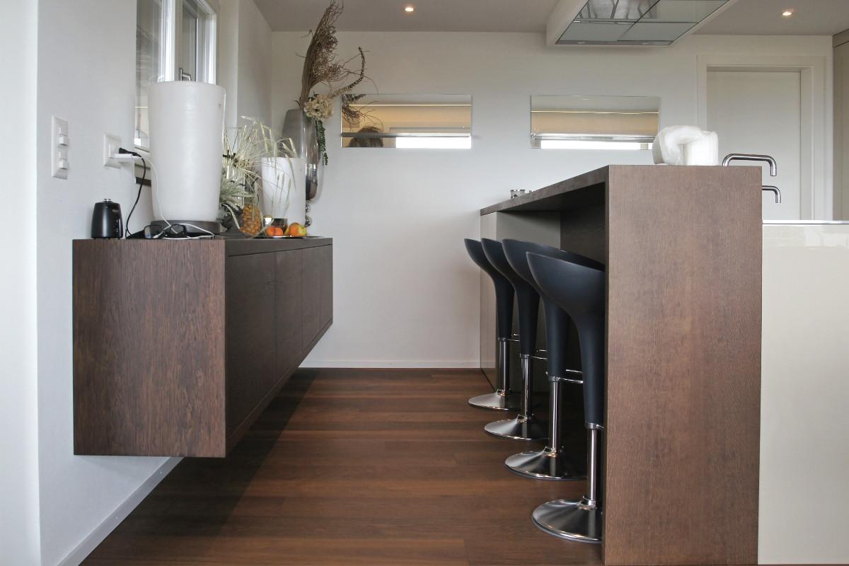 Küchenzeile mit Barelement und beigefügtem Sideboard.