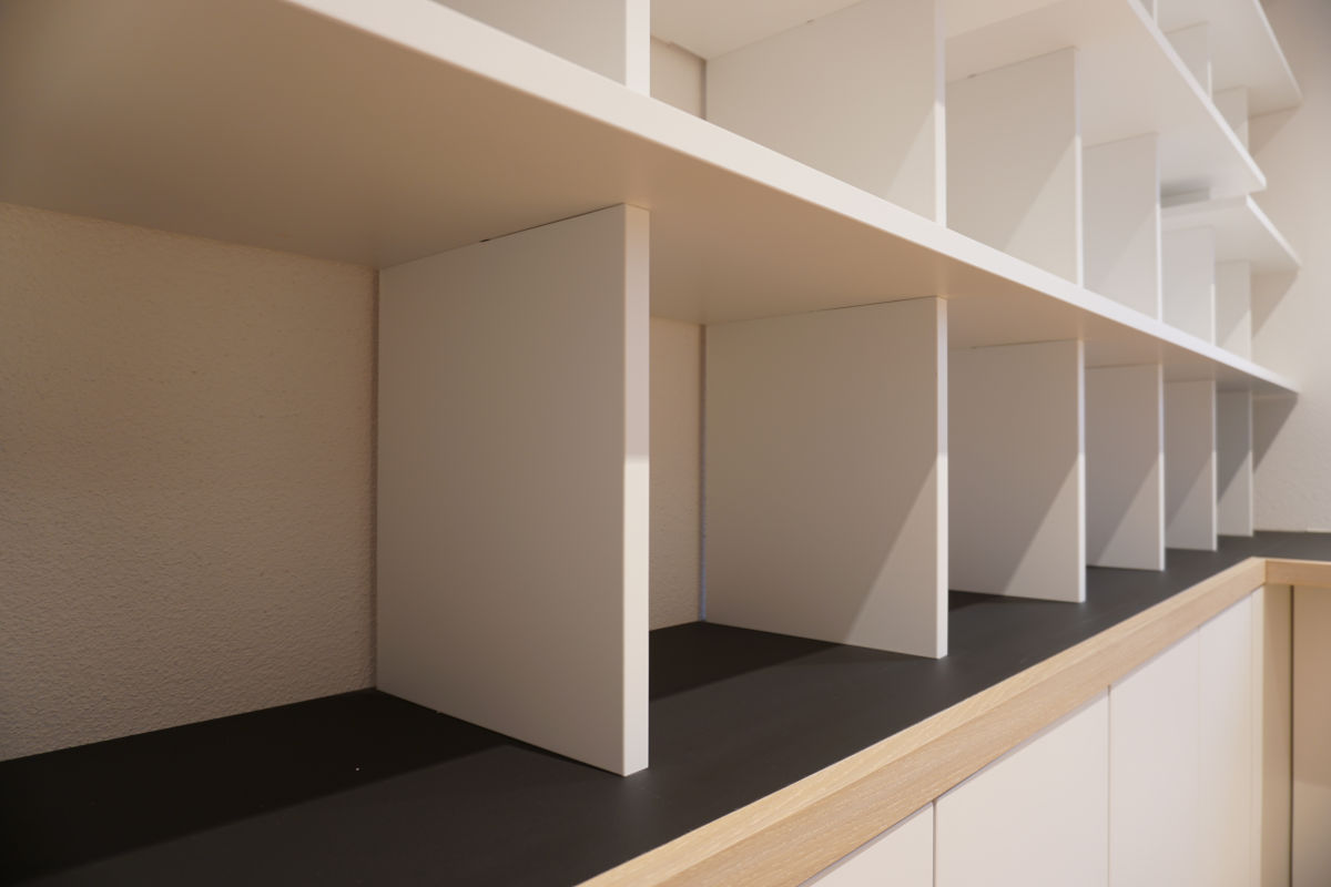 Detail vom  Bücherregal: Die Fächer stehen auf einem Sims mit schwarzem Linoleum-Belag (Desktop), abgeschlossen von einer massiven Eichenholz-Kante.