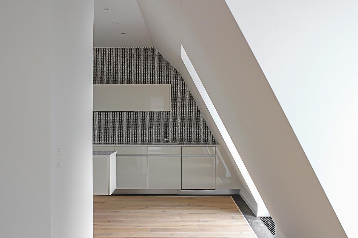 Hinter der Wand links schaut die schwebende Kücheninsel hervor.