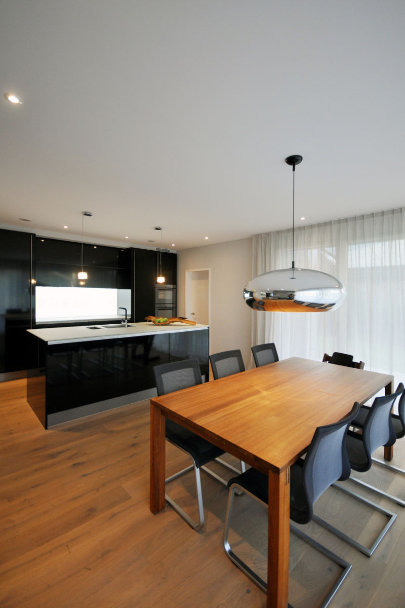 Auf dem schönen Parkett-Boden tritt die dunkle Küche besonders edel hervor.