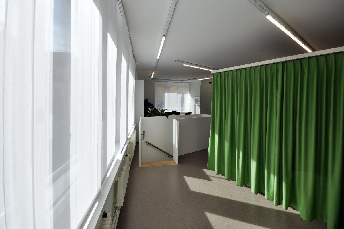 Die neue Garderobe ist durch einen knallig grünen Vorhang abgetrennt