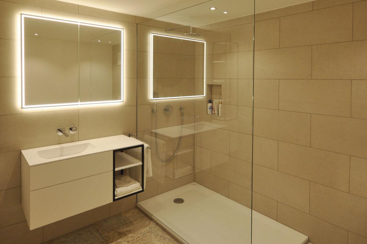 Edles Badezimmer mit grossflächigen Kacheln. Badmöbel von Talsee. Hinerleuchteter Spiegel.