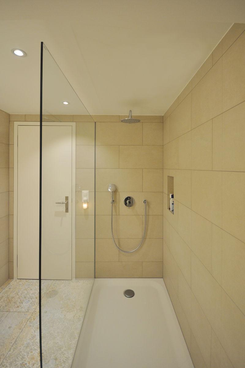Dusche mit Nische für Pflegeprodukte. Puristische Armaturen mit Regenbrause.