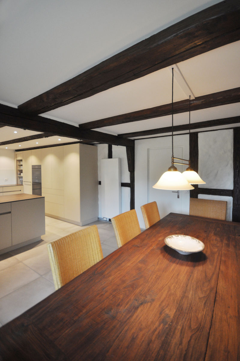 Der dunkle Holztisch kontrastiert schön mit der Hellen Küche.