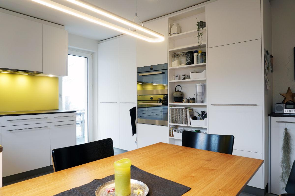 Helle schlichte Küche mit weissen Fronten und gelber Glasrückwand