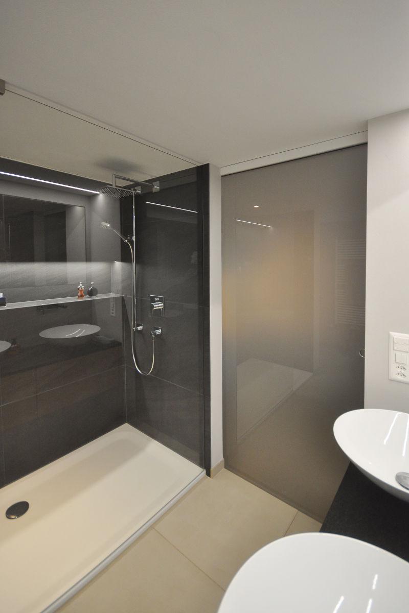 Die Dusche mit Glastrennwand ist schwellenlos begehbar.