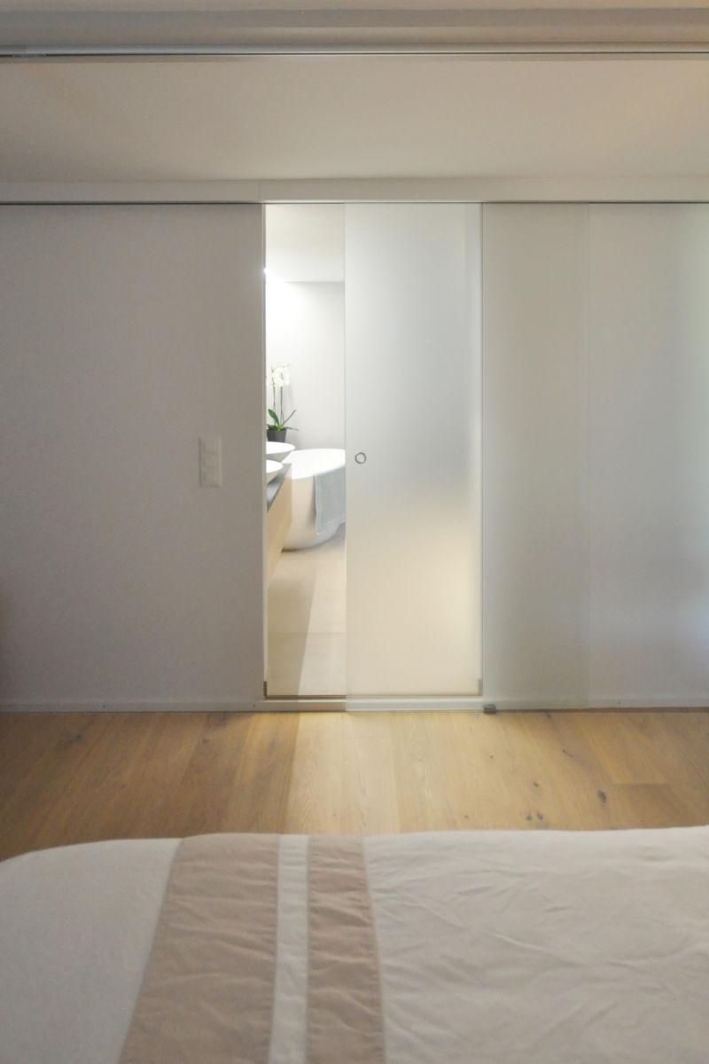 Das Bad und der begehbare Kleiderschrank sind mit einer Glasschiebetür vom Schlafzimmer getrennt.