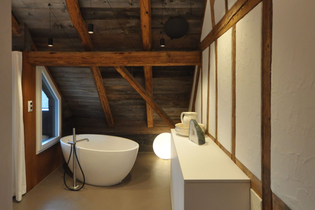 Badezimmer mit freistehender Badewanne im Dachstock eines Fachwerkhauses.