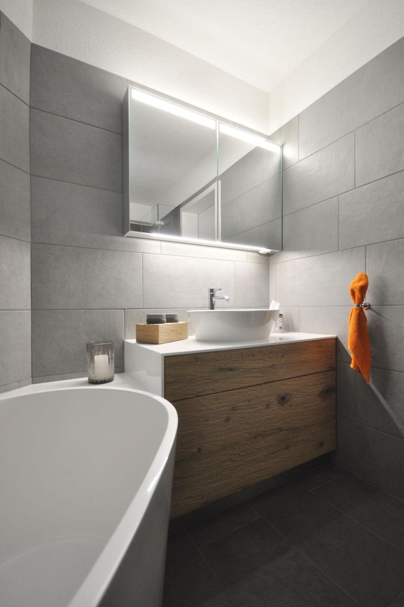 Waschtischmöbel und Badewannenverkleidung bilden eine Einheit