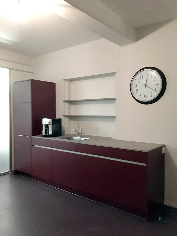 Teeküche mit dunkelroten Fronten, Abdeckung aus einem Beton-Imitat.