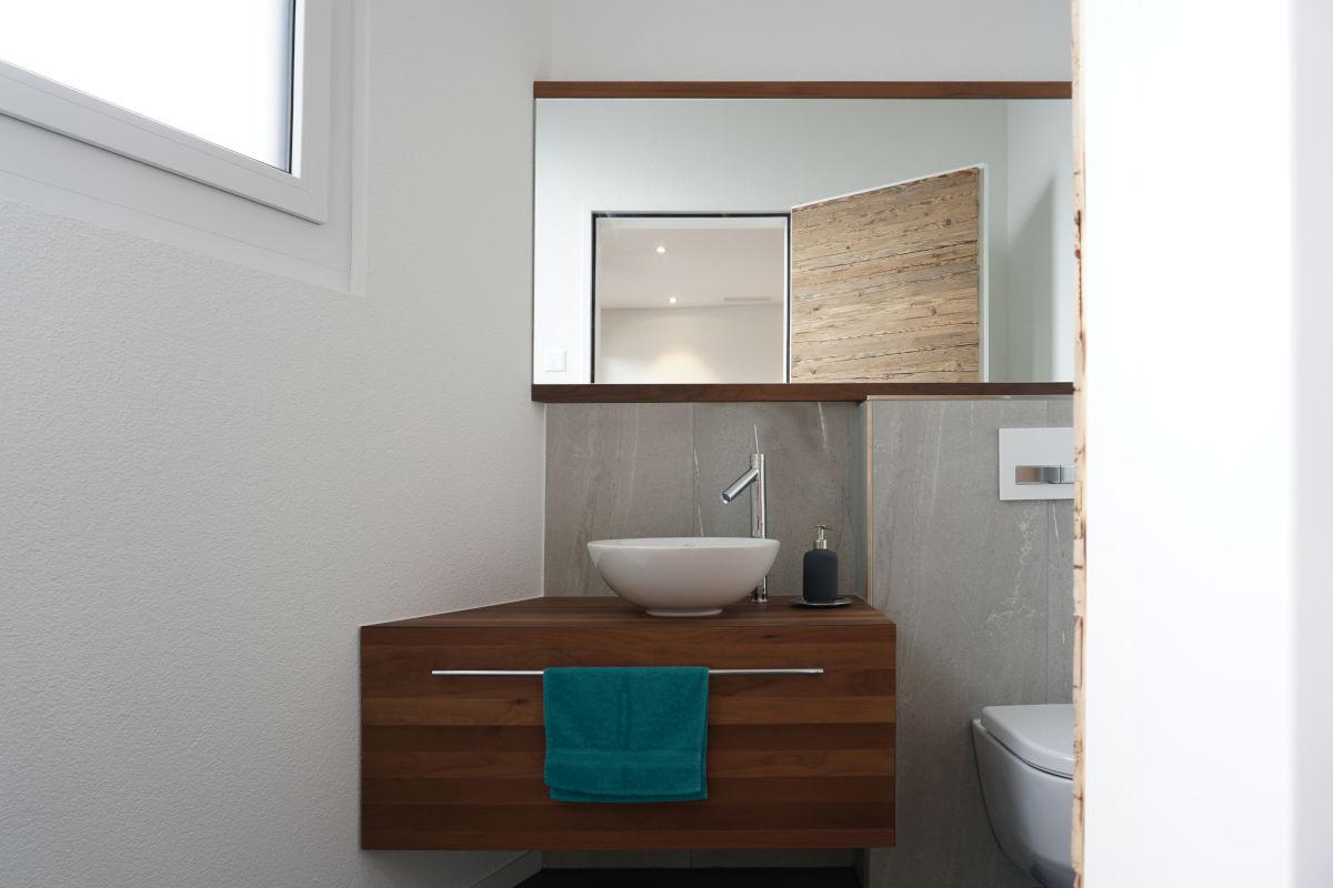 Das Badmöbel ist aus massivem amerikanischem Nussbaum auf Gehrung gefertigt. Der Spiegel ist flächenbündig auf die ganze Wandbreite eingebaut.