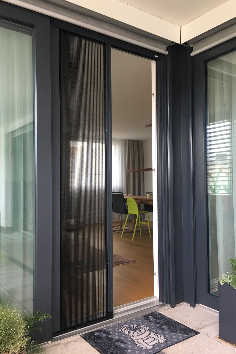 Die halboffene Insektenschutz-Tür ist platzsparend eingebaut und die Farbe ist exakt auf die Fenster abgestimmt.