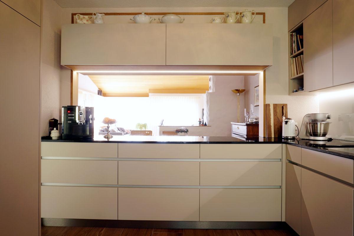 Die Küchenmöbel haben helle Fronten mit Alu-Griffmulde.