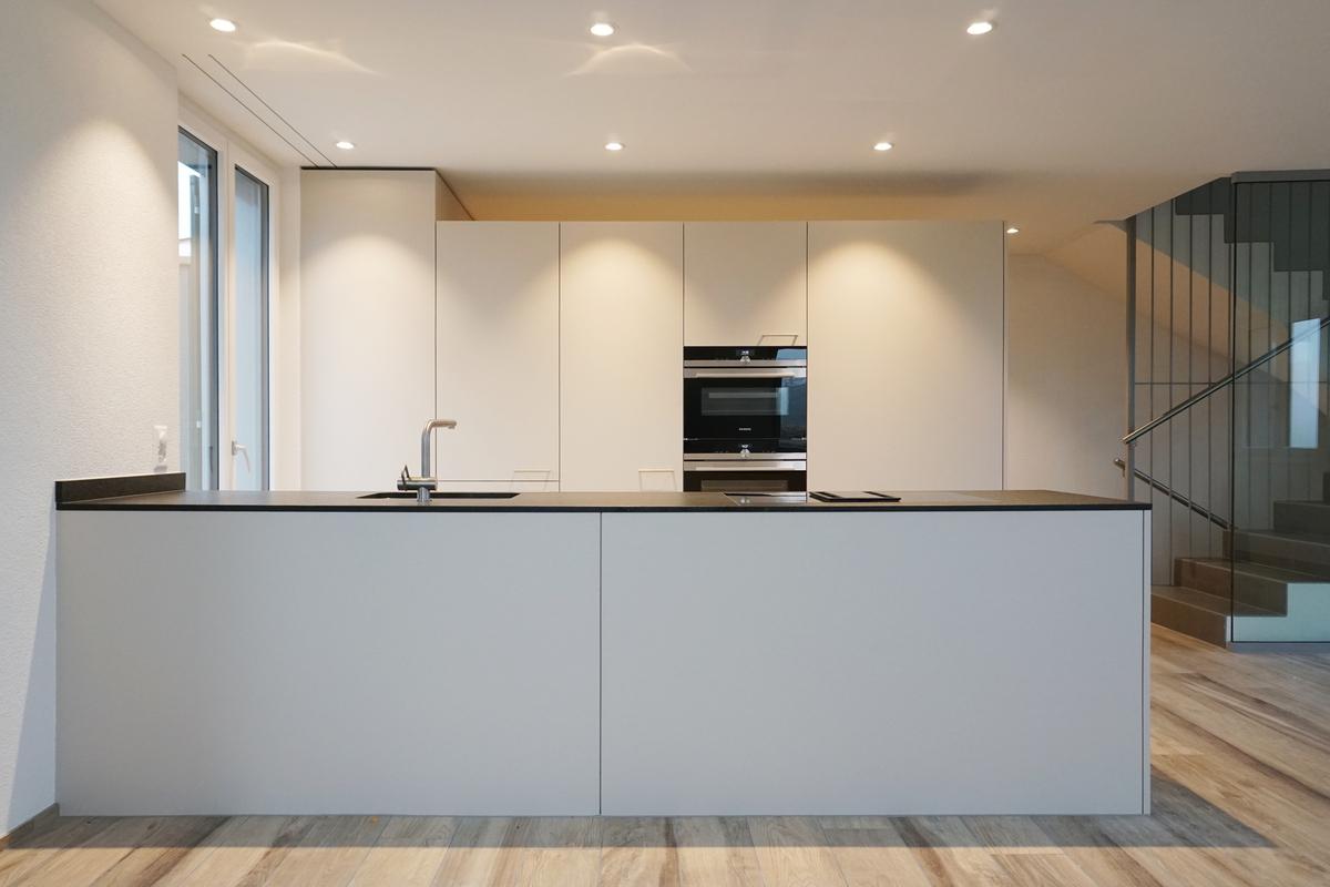 Klare Formen, dezente Farben und eine elegante Abdeckung zeichnen diese Küche aus.
