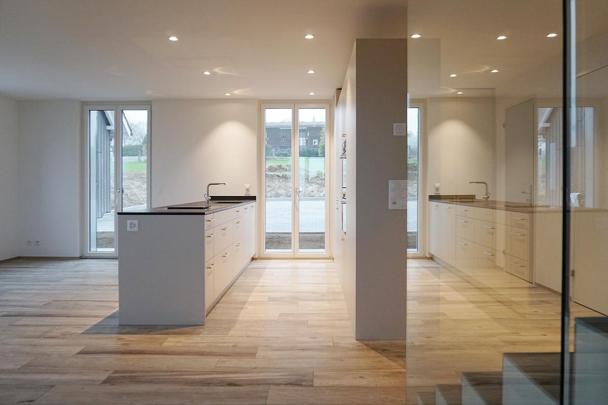 Moderne offene Küche. Deren Rückseite ist gleichzeitig die Garderobe