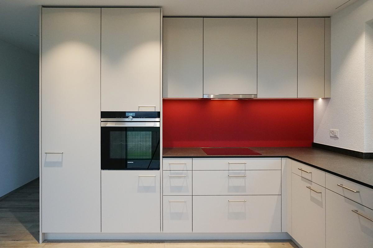 Auch diese Küche hat auf einer Seite eine rote Rückwand