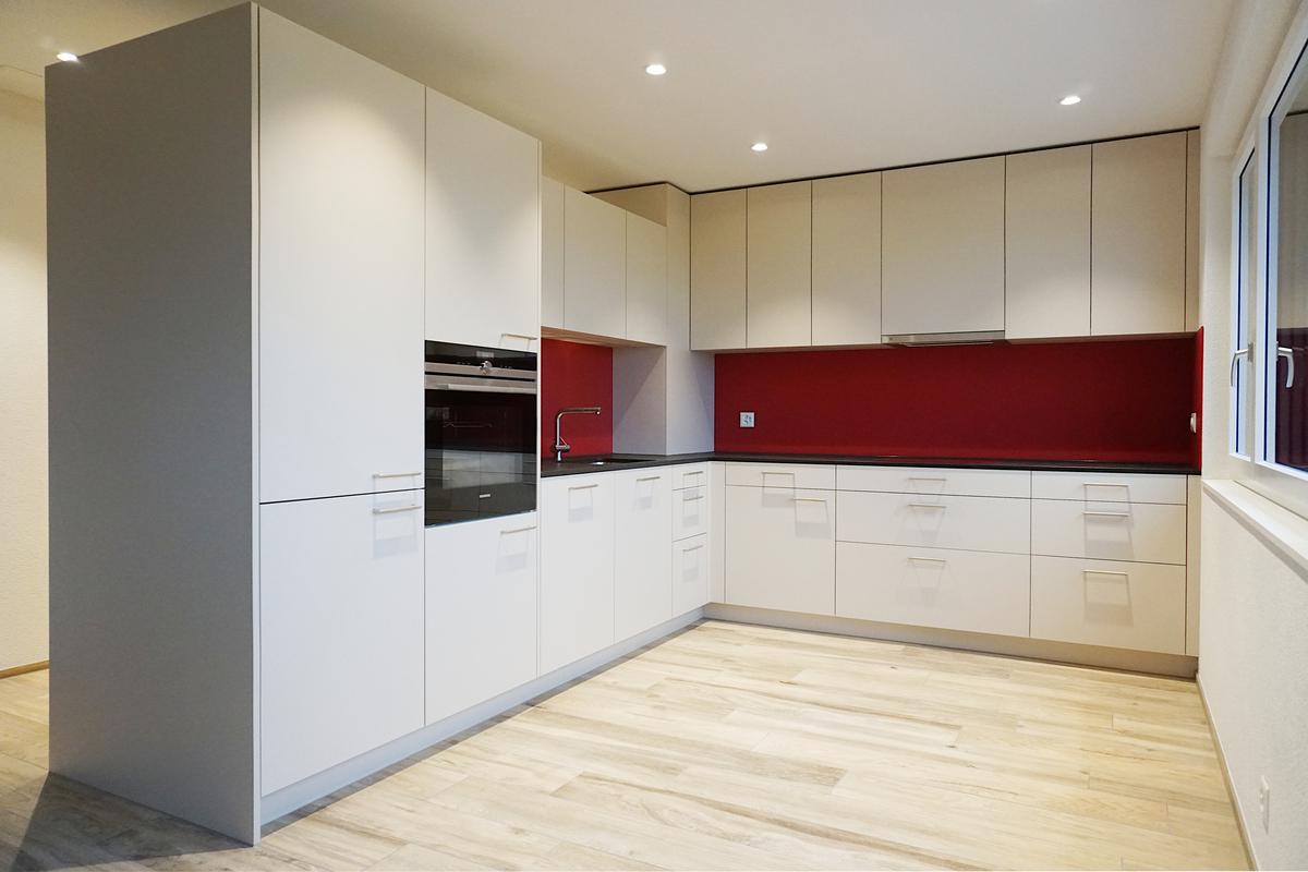 In der zweiten Wohnung steht eine moderne L-Form Küche mit roter Rückwand