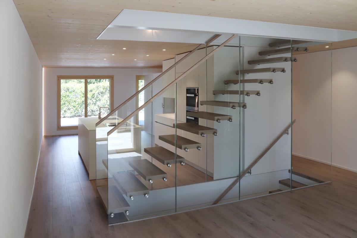 Das Treppengeländer aus Glas lässt genügend Licht hindurch zur Küche.