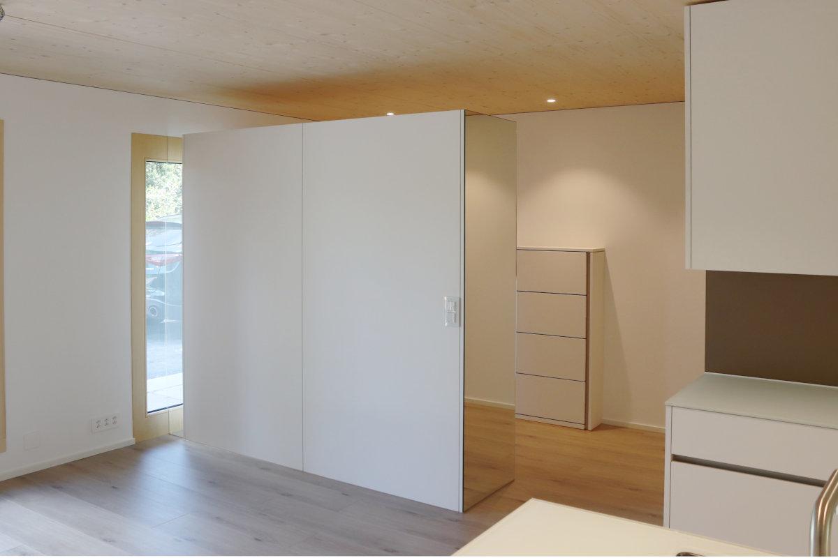 Frei stehende Garderobe, hinten an der Wand ein Schuhregal mit aufrechter Griffleiste.