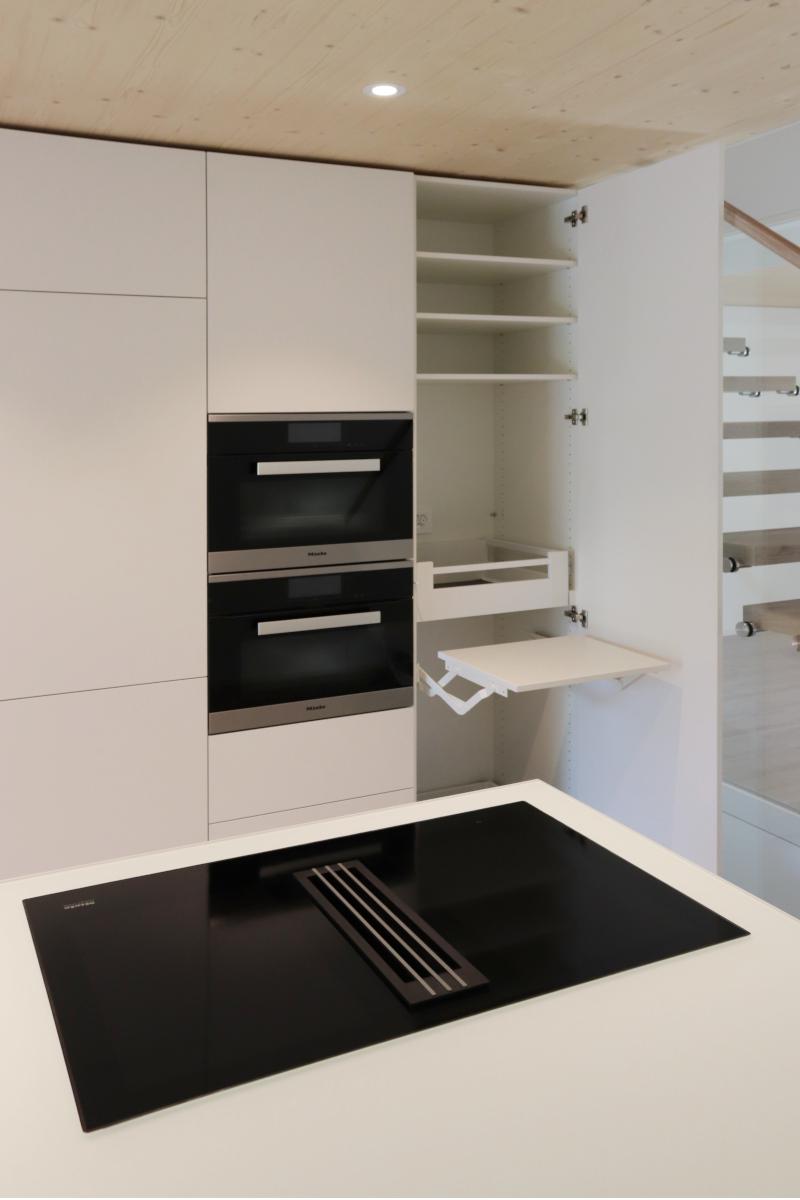 Miele Kochfeld mit integriertem Tischlüfter. Hinten Schwenktisch für einen Reiskocher.