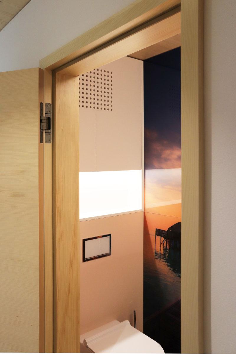 Wandmöbel mit beleuchteter Nische und integrierter Lüftung.