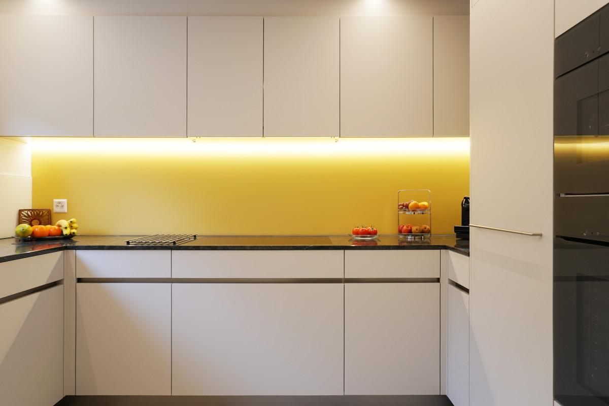 Helle Küche mit gelber Glasrückwand