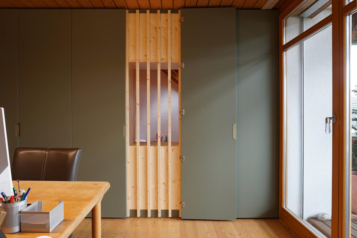 Ein Schrank als Raumtrenner. Hinter einer Schranktür befindet sich ein Fenster mit senkrechten Holzlamellen.