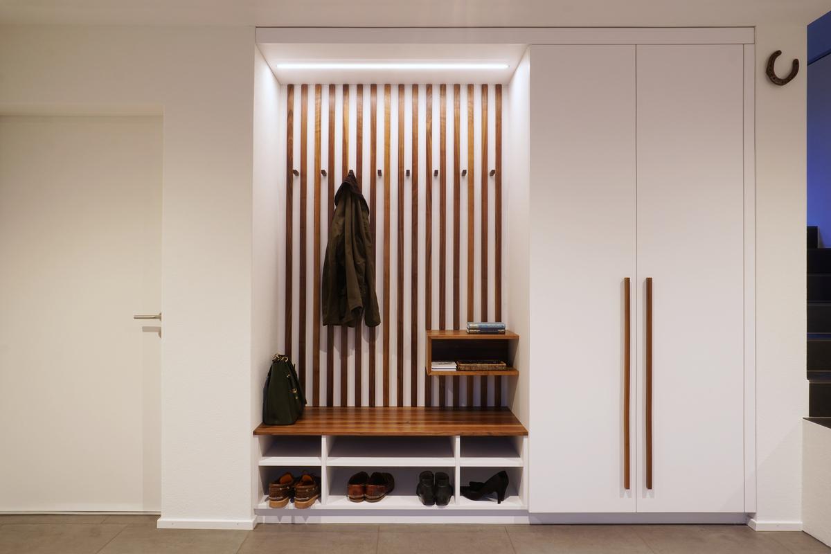 Grosszügige Garderobe; die Sitzbank, das Ablagefach sowie die Holzlamellen sind aus amerikanischem Nussbaum gefertigt.