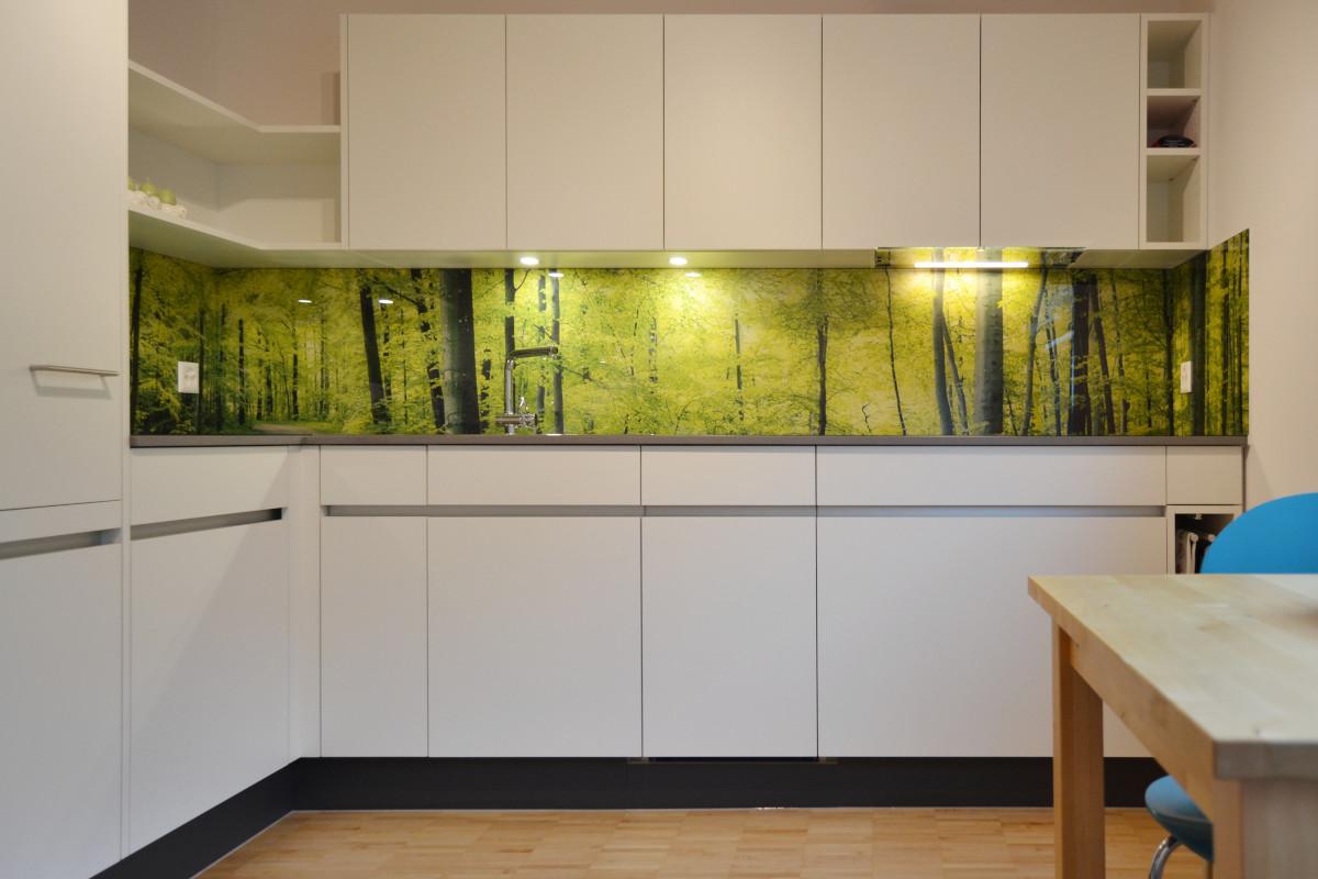 Dank dem Waldmotiv auf der Glasrückwand wirkt die Küche sehr geräumig.