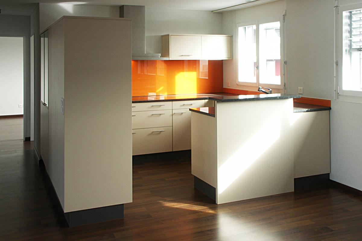 Helle Küche mit auffallender orangen Glasrückwand.