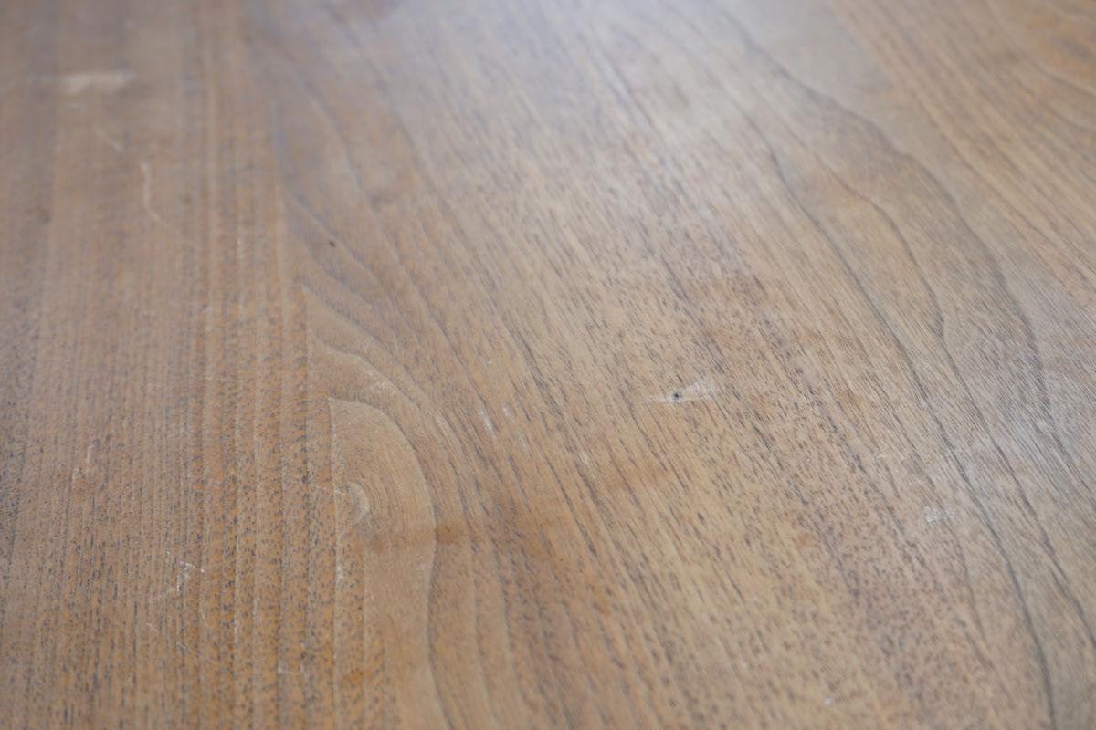 Kratzer, Löcher und Wasserflecken auf der Tischplatte vor der Reparatur.